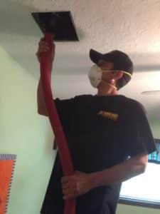 Extreme Air Duct Cleaning Houston, TX technician cleaning an air duct in the ceiling
